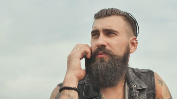 Brutal bearded man talking on the phone and smokes a cigarette.