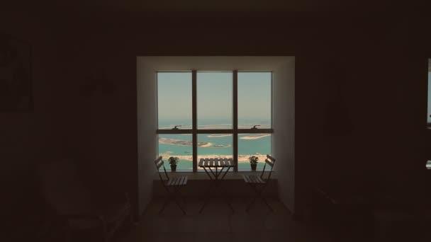 Pohled z okna na Palm Jumeirah v Dubaji. Střelba v pohybu.