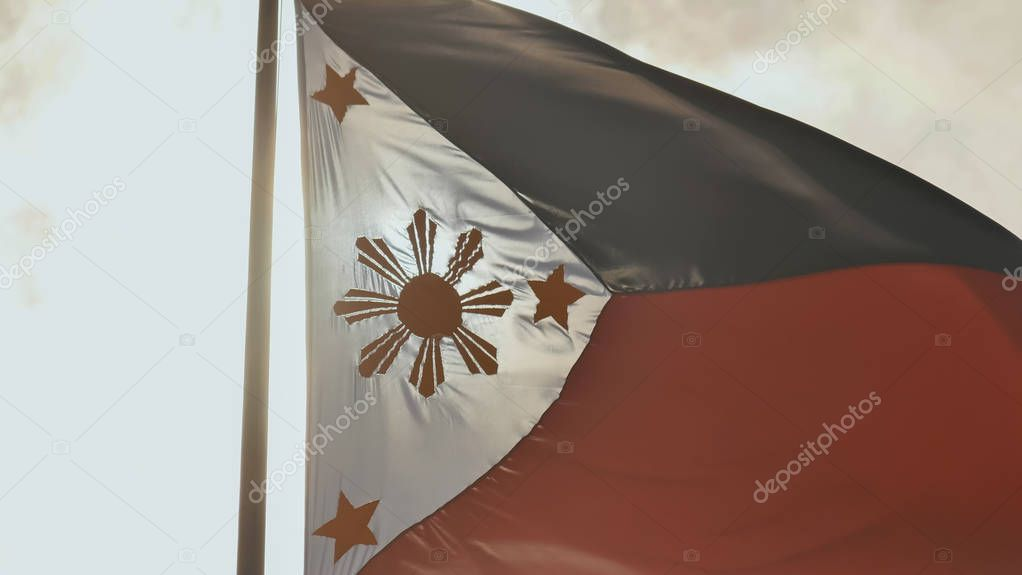 Flying bicolor flag of the Philippines with central golden sun representing the provinces and stars the islands.