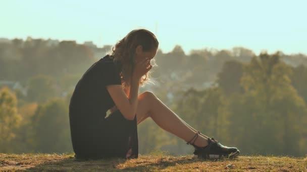 Szomorú lány sziluettje sit egyedül a fű olyan magányos, és sírni.