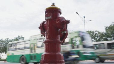 Red fire hydrant poles on street Ho Chi Minh city. Next to the road and passing cars and motorcycles. Vietnam.