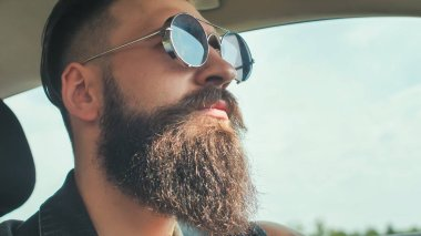 A brutal bearded man in sunglasses is driving a car.