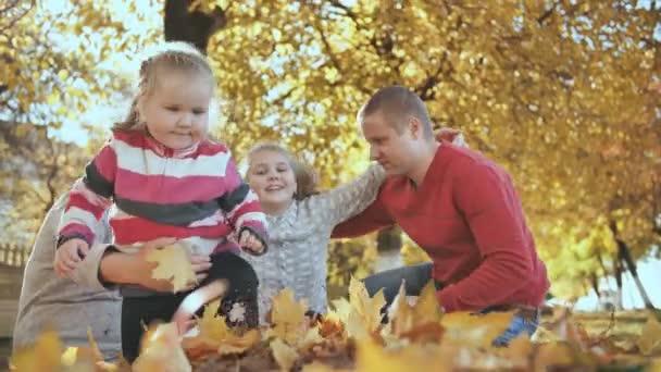 Šťastná rodina je všeobjímající za slunečného podzimního počasí.