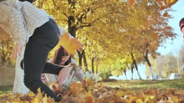 Šťastná rodina venku hrát s padlé listí za slunečného podzimního počasí.