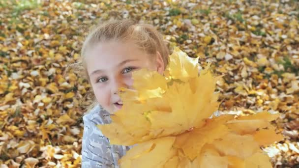 Usmívající se dospívající dívka pózuje s podzimní listy