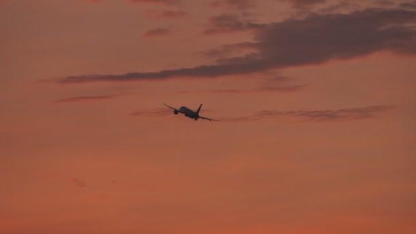 Startende Flugzeuge gegen den Abendhimmel nach Sonnenuntergang.