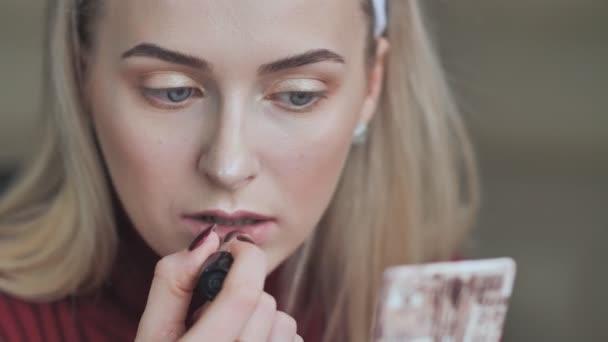 Blonďatá dívka namaluje rty s rtěnkou s temně červené barvy.