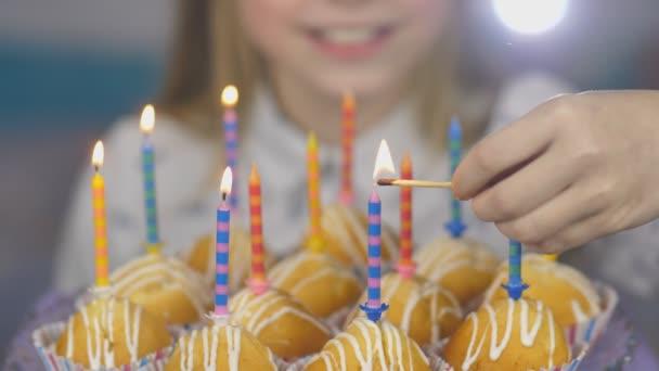 Dospívající dívka světla svíčky na dort na její narozeniny