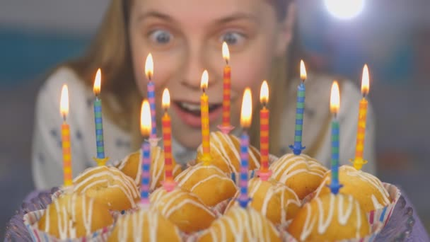 Teen girl admires burning candles at cake on her birthday.