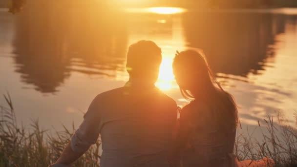 Egy fiatal pár ül a tavon naplementekor..