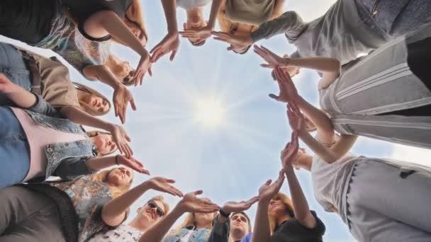 Velká skupina studentů vytváří kruh z rukou.