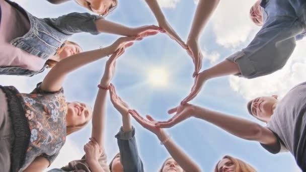 konzeptionelles Symbol der Zusammenarbeit verschiedene Hände, die einen Kreis bilden. Schüler helfen sich gegenseitig.