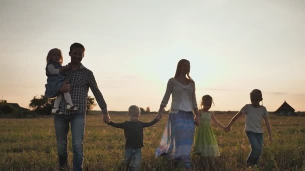 Při západu slunce chodí po podlaze velká rodina šesti lidí.