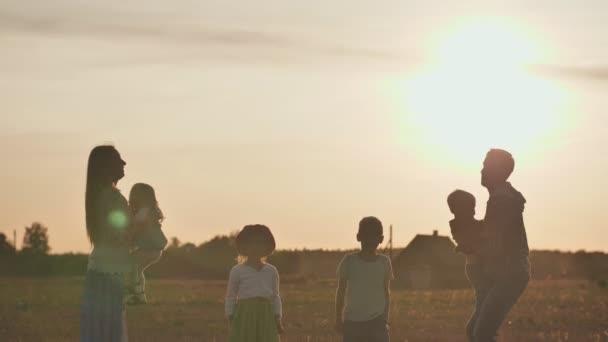 Koncept šťastné velké rodiny. Šťastní rodiče, jak vyhazují děti do pozadí při západu slunce.