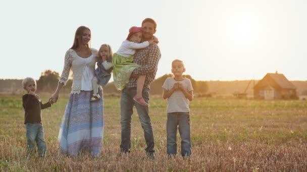 Velká rodina na pozadí večerního západu slunce.