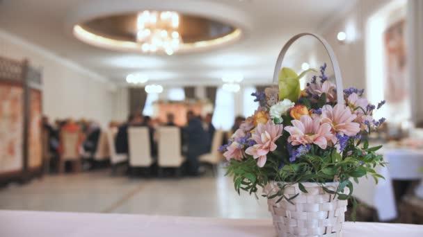 Koncept svatební oslavy. Kytice květin na pozadí hostiny hosty, kteří jedí.