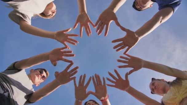 Freunde formen aus den Handflächen einen Kreis.