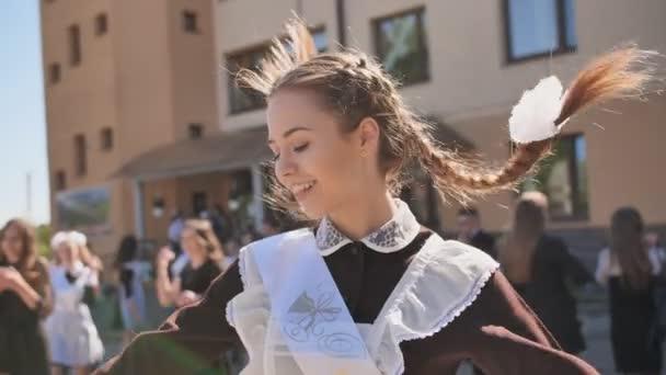 Šťastná ruská dívka absolvent fouká polibek v den promoce.