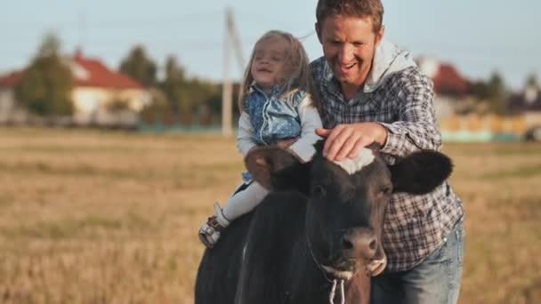 Otec zasadil jednoletou dceru krávě a pózuje..