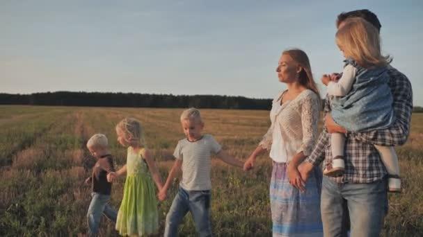 Velká rodina kráčí po poli při západu slunce.