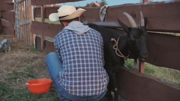 ein junger Mann melkt seine Ziege im Dorf.