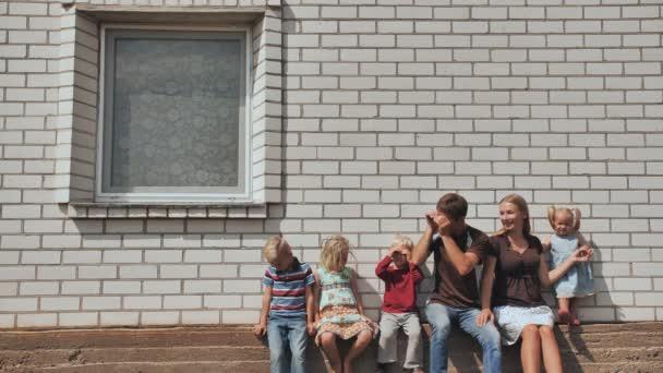 Velká rodina se čtyřmi dětmi před vlastním domem.