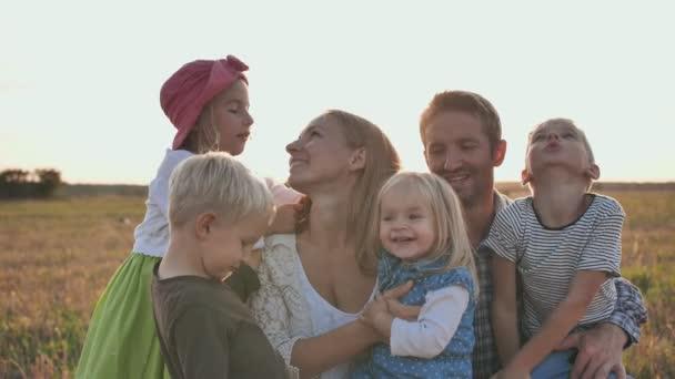 Rodina 6 lidí na pozadí mírného západu slunce.