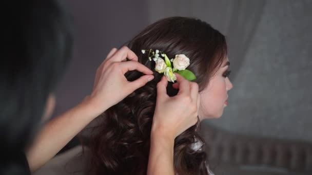 The stylist adorns the girls hair with delicate flowers.