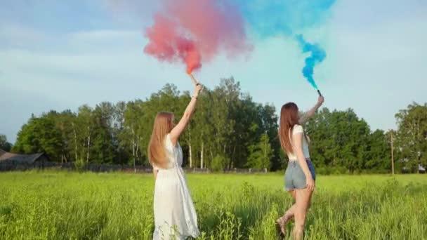 Zwei glückliche Mädchen sprühen bunten Rauch.
