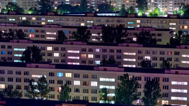 Včasnost obytných čtvrtí nočního města s rozsvícenými světly z oken apartmánů.