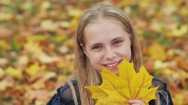 A young girl of 13 years old with autumn leaves poses in front of a video camera.