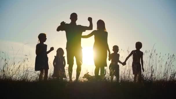 Silhouetten einer glücklichen großen Familie, die vor dem Hintergrund des Sonnenuntergangs tanzt und sich umarmt.