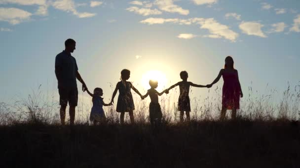 Happy large family at sunset with a dog.