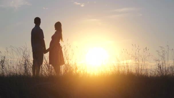 Siluety šťastných mladých rodičů na pozadí večerního slunce.
