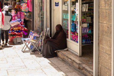 Jerusalem, Israel, June 13, 2020 : Muslim woman dressed in hijab sits and begs in the Arab quarter in the old city of Jerusalem, Israel