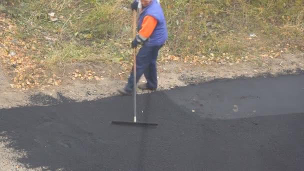 Silnice, ulice, oprava funguje. Zaměstnankyně během asfaltování silnice. Těžké ženské ruční práce ve stavebnictví