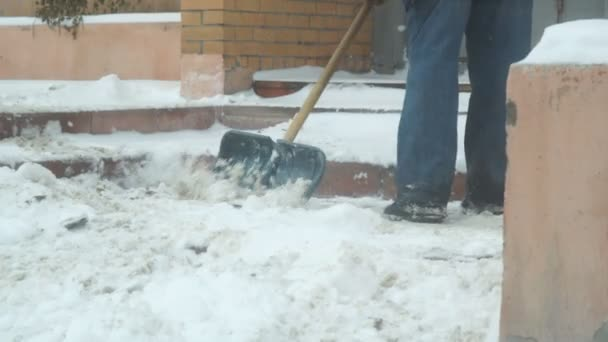 Man cleans snow with shovel