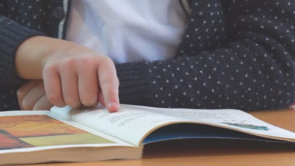 Schoolboy reading, moving fingers on book