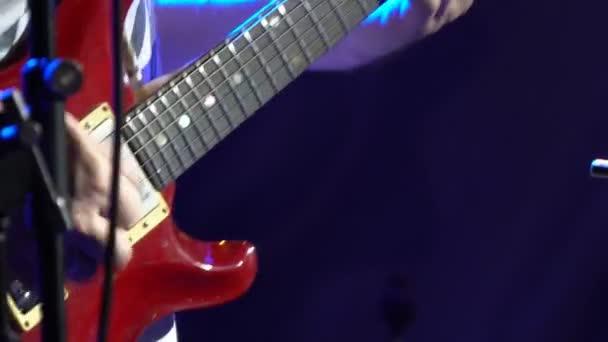 Gitáros rock banda gitározik a színpadon reflektorfényben