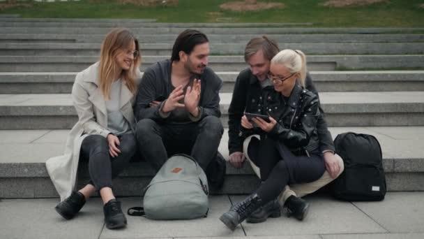 Gruppo di quattro amici ridere ad alta voce allaperto, condivisione di umore buono e positivo, felice friends studenti sulla strada parco, campus universitario, gente sorridente del telefono
