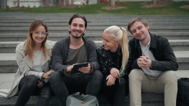 Group of four friends laughing out loud outdoor, sharing good and positive mood, happy friends students on street park, university campus, phone smiling people