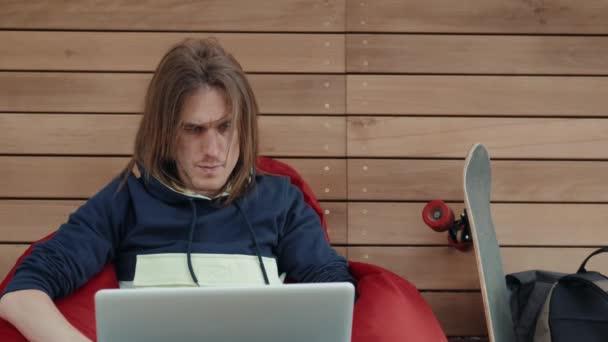 Net-könyv első laptop számítógép fiatal üzleti ember munka ül alatt a reggeli kávé modern bolt loft hosszú haj tervező kreatív férfi szabadúszóként hátulnézet