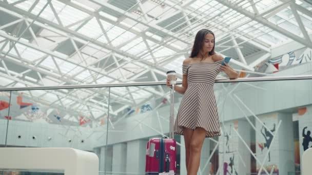 Vásárlás a nő mosolyogva beszél a telefonon, a mall táskákkal. Gyönyörű lány, smartphone, a bevásárlóközpont, vagy a repülőtéri terminál bőrönd poggyász.
