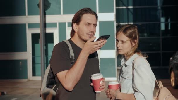 Volný čas, technologie, komunikace a lidé koncept - mladý muž a žena pomocí hlasových příkaz rekordér pomocníka nebo volání na smartphone na ulici, studenti hlasové rozpoznávání zprávu s kávou