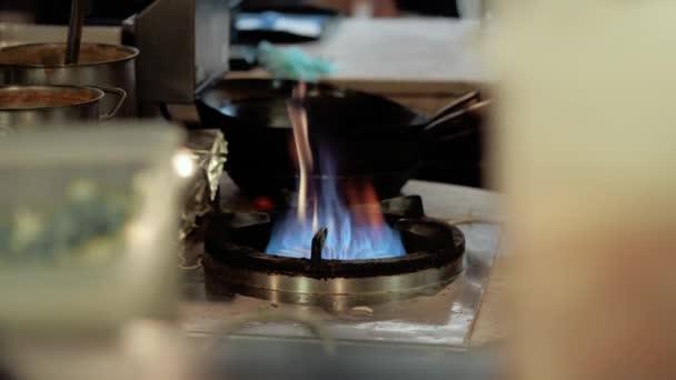 Šéfkuchař v restauraci kuchyni na sporáku pan, dělá flambe na potraviny