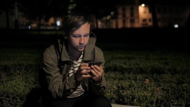 Férfi hang felismerés intelligens telefon park night hotelben szabadtéri, diák férfi használja üzenet audio segítő kereső buszmegálló metró metró állomás