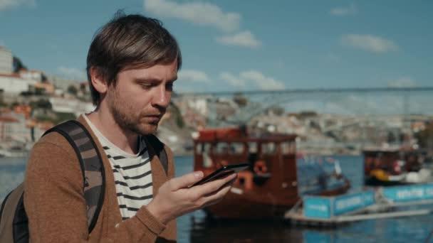 Fiatal férfi ült-beszélgetést a Hangrögzítõ üzenetet hang ai beszéd telefon smartphone kívül a naplemente silhouette tengerpart hajók hajón.