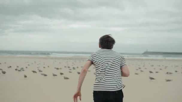The boy happy man male tourist runs along the beach lake promenade and chases pigeons seagulls gulls birds ocean freedom coastline .