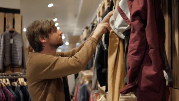 Man chooses sports clothes in a store shopping mall young student casual clothing buy checkout paying