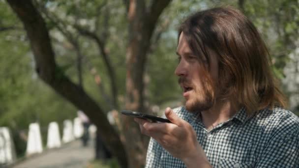 Csípő ember elküldés hang üzenet-val mozgatható telefon-on Park, audio hang felismerés AI beszéd segítő beszélgetés telefon